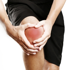 Studio shot of young man with knee pain