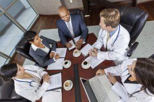 Interracial group of business men & women, businessmen and businesswomen and doctors team meeting in hospital boardroom